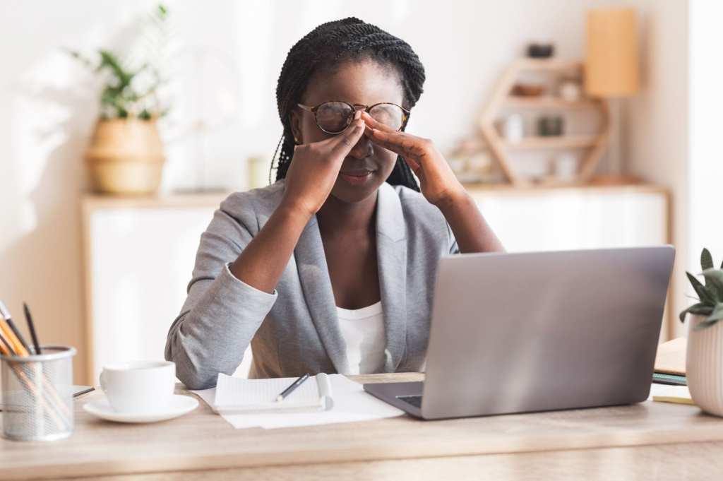 Mulher de frente para o notebook, com óculos suspenso, segurando os olhos