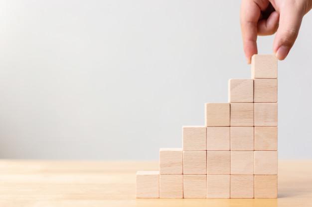 Uma mão, empilhando blocos de madeira
