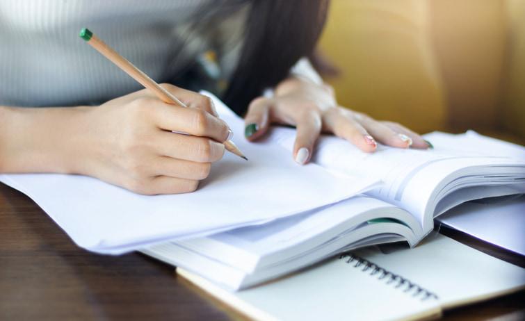 Uma mão feminina, segurando um lápis, escrevendo em uma folha, em cima de um livro.