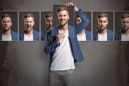 Homem de calça, camiseta, blazer, segurando sua foto, a frente do rosto, e atrás dele, na parede, varias fotos dele, mostrando varias emoções