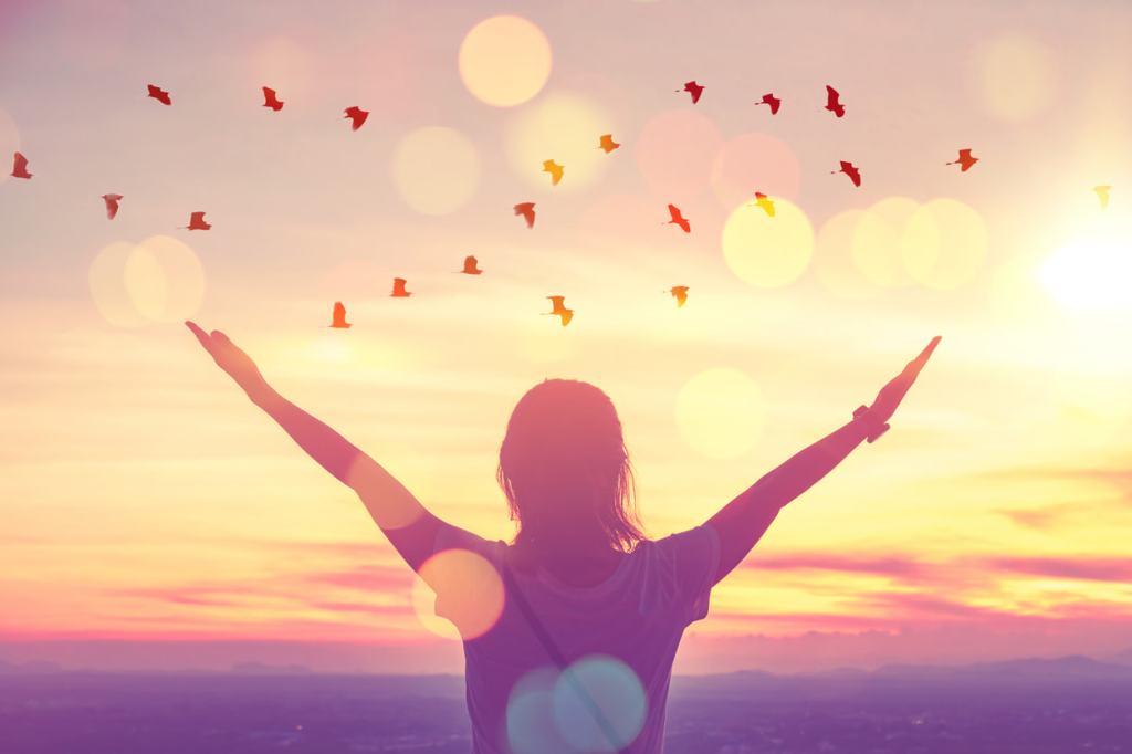 Mulher com os braços para o alto, contemplando os pássaros no céu