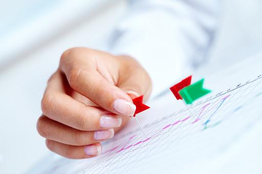 Mão de uma mulher, colocando marcadores, em uma tabela