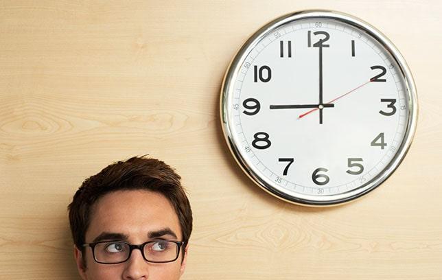 Imagem de um homem, olhando para um relógio acima da cabeça